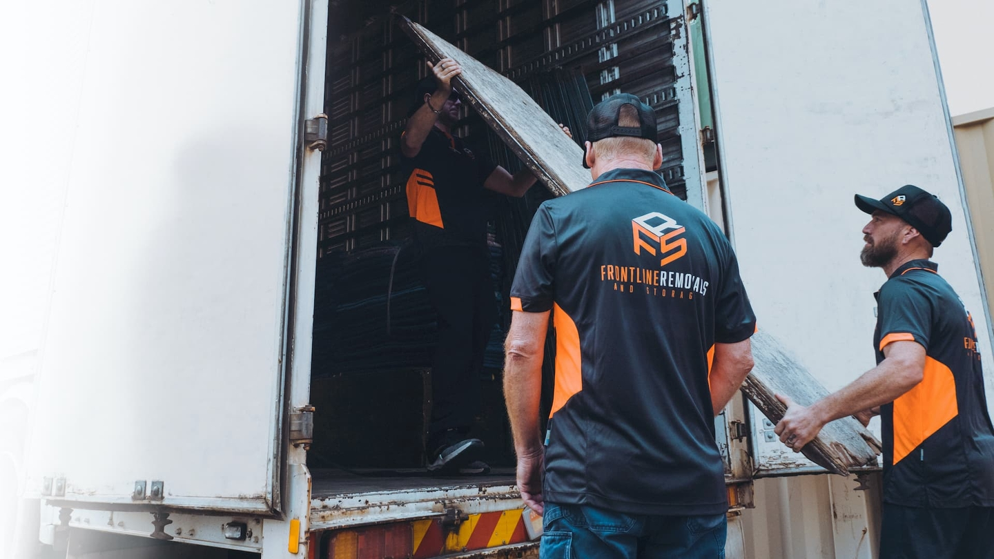 Frontline removalist crew loading materials in trailer truck